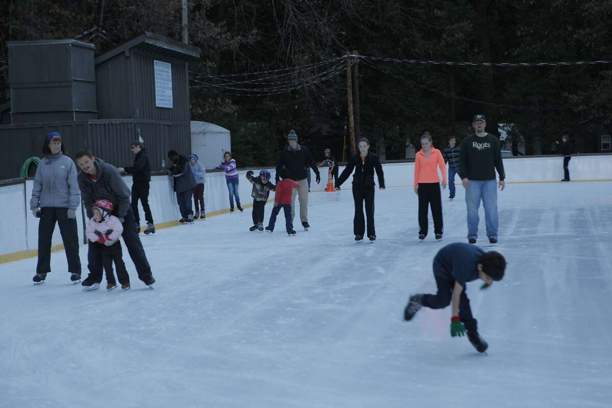 A kid goes kerplunk as youngsters and adults alike ice skate at the outdoor rink in Yosemite Valley, the Curry Village Ice Rink.