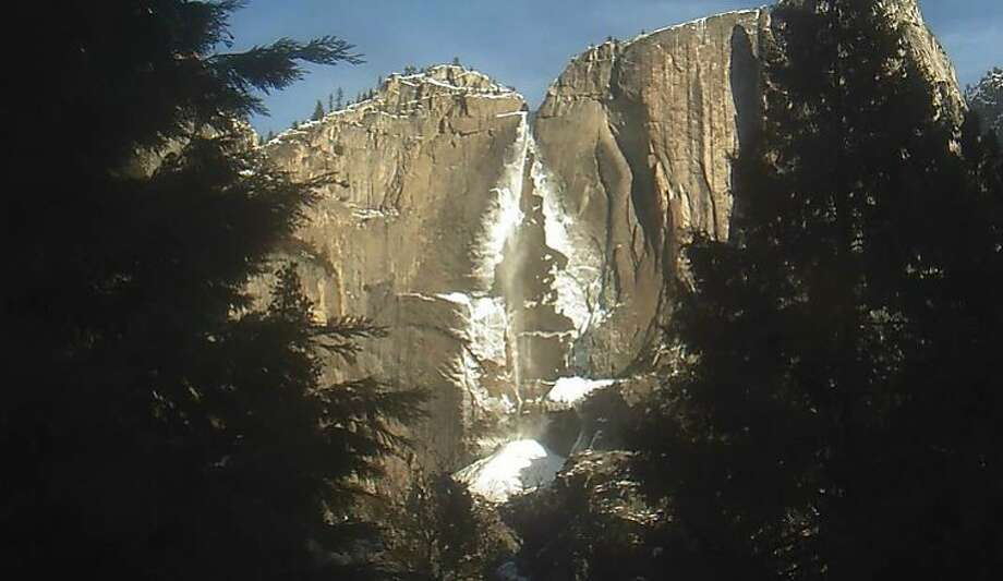 """When morning light illuminated Yosemite Valley this week, the upper tier of Yosemite Falls was a thin stream of silver, its edges cast in ice, and the first drop fell 1,400 feet to a jumble of boulders glazed in Arctic white. Photo: Yosemite Conservancy, Special To """"The Chronicle"""