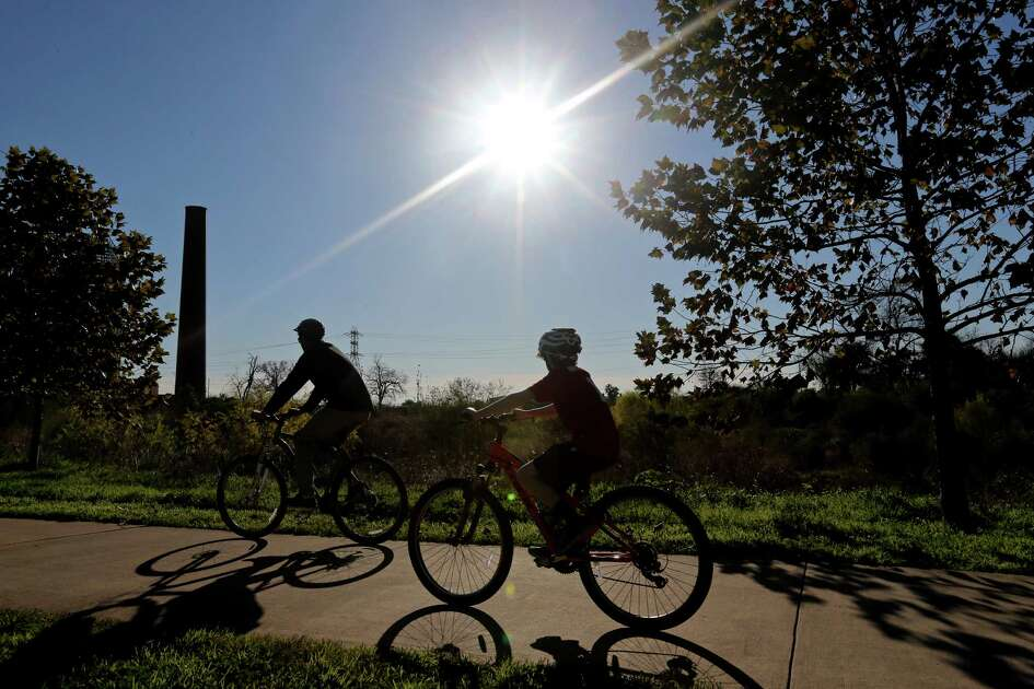 Enjoying the sunny weather cyclists ride on the Mission Reach trial of the San Antonio River Monday Jan. 4, 2016.