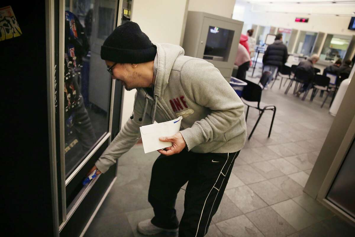 Will Nacor (left) of San Francisco picks up his selection after making a purchase from a vending machine at the SFMTA customer service center on Monday, January 11, 2015 in San Francisco, Calif.