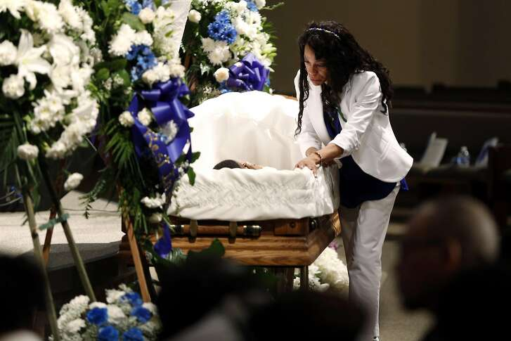 Audrey Hughes Cornish stands over her son Torian Hughes during his funeral at Shiloh Church in Oakland, California, on Monday, Jan. 11, 2016.