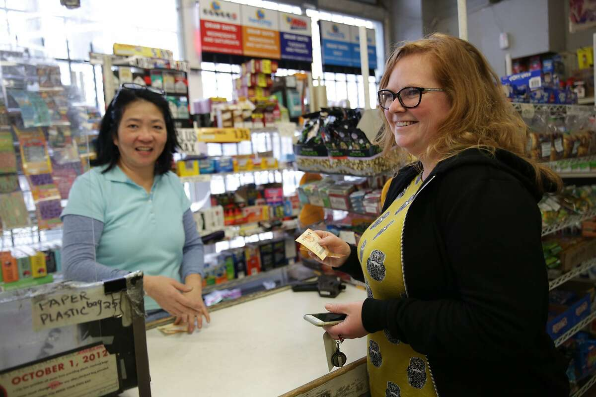 Laura Olson (right) of Oakland talks with Mary Yu, Unimart owner, after purchasing a Power Ball ticket with winnings at Unimart on Monday, January 11, 2015 in San Francisco, Calif.
