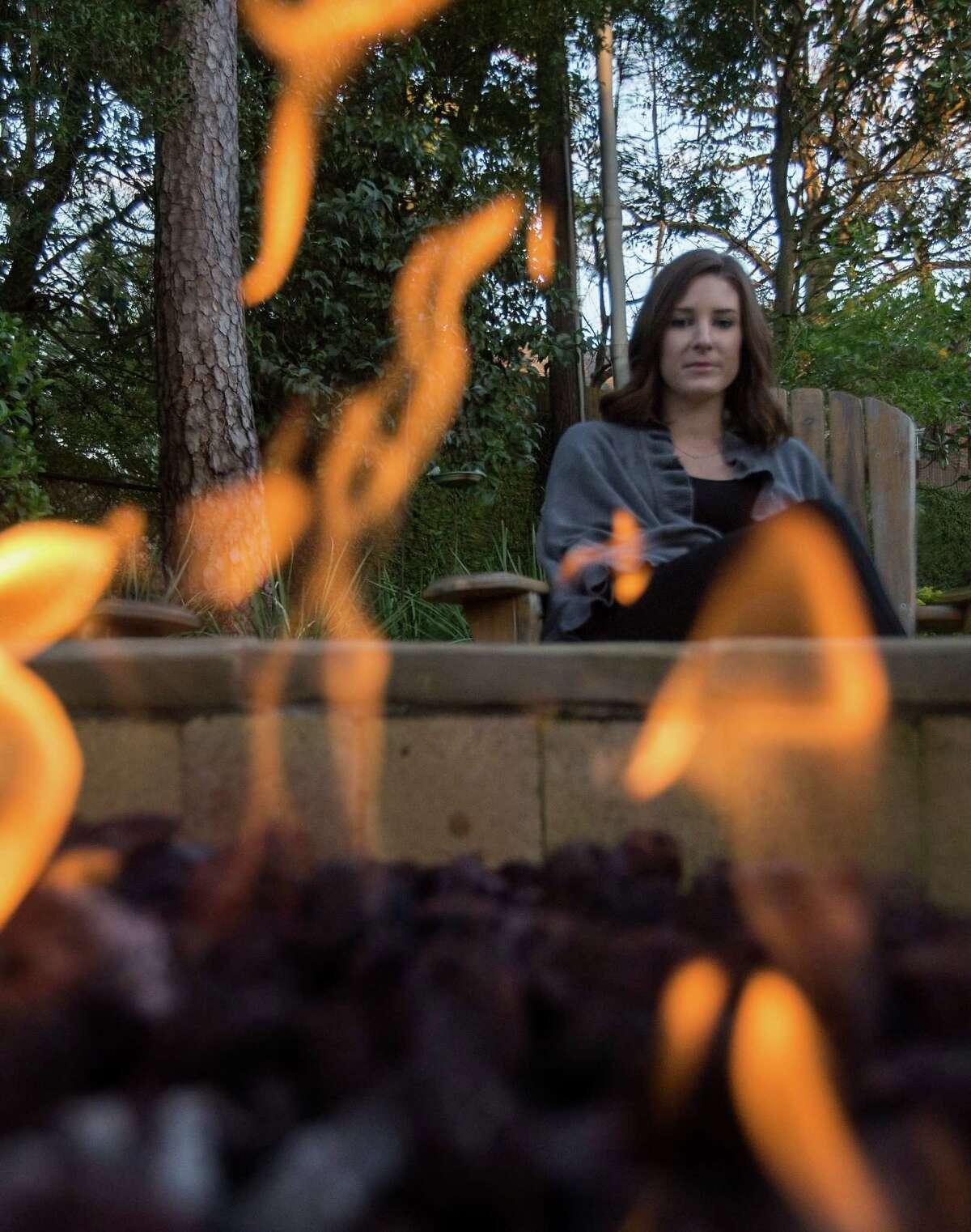 Stephanie Dishman sits next to her parents' custom-built fire pit in their backyard Thursday, Jan. 7, 2016, in Houston. ( Jon Shapley / Houston Chronicle )