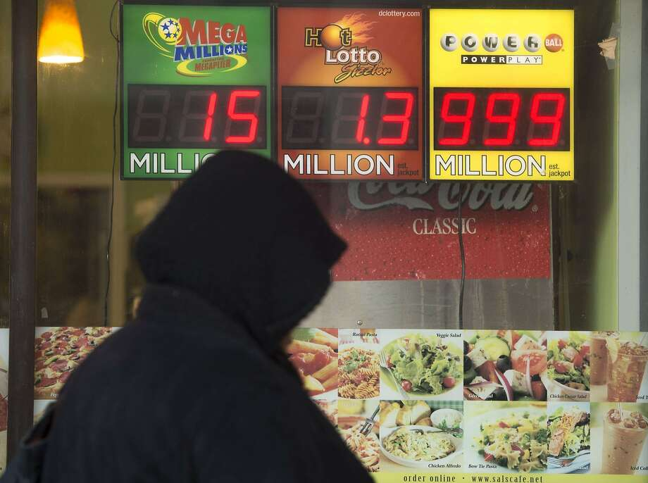 A woman walks past a sign showing a Powerball prize of $999 million, the largest jackpot winnings that the Powerball sign can display, with the actual Powerball jackpot estimated at $1.3 billion, outside a deli in Washington, DC, January 11, 2016. Photo: Saul Loeb, AFP / Getty Images