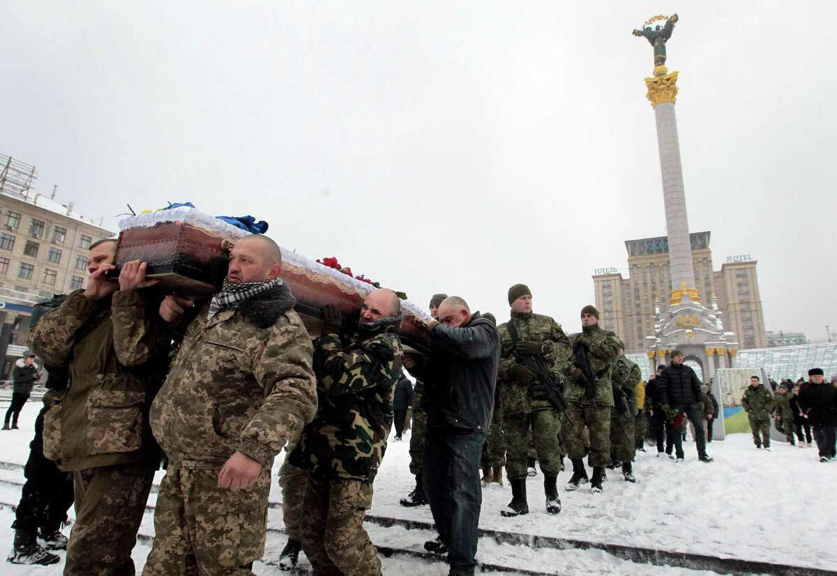 Ukrainian soldiers carry the coffin bearing the body of police captain Oleksandr IlnItsky, who was shot dead by a pro-Russian sniper in the war conflict-hit Donetsk region, during a commemoration ceremony in Independence Square in Kiev, Ukraine, on Monday, Jan. 11, 2016. IlnItsky was killed on Jan. 9 as he was rescuing civilian residents from the fire by pro-Russian separatists.