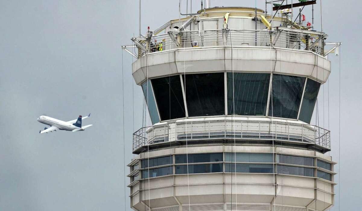 A passenger jet flies past the FAA control tower at Washington's Ronald Reagan National Airport. (AP Photo/Cliff Owen, File)