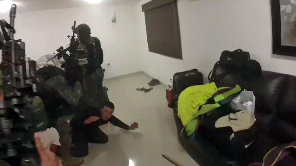 In a frame-grab from video taken Friday, Jan. 8, 2016, Mexican navy marines storm a home during the operation to recapture drug kingpin Joaquin
