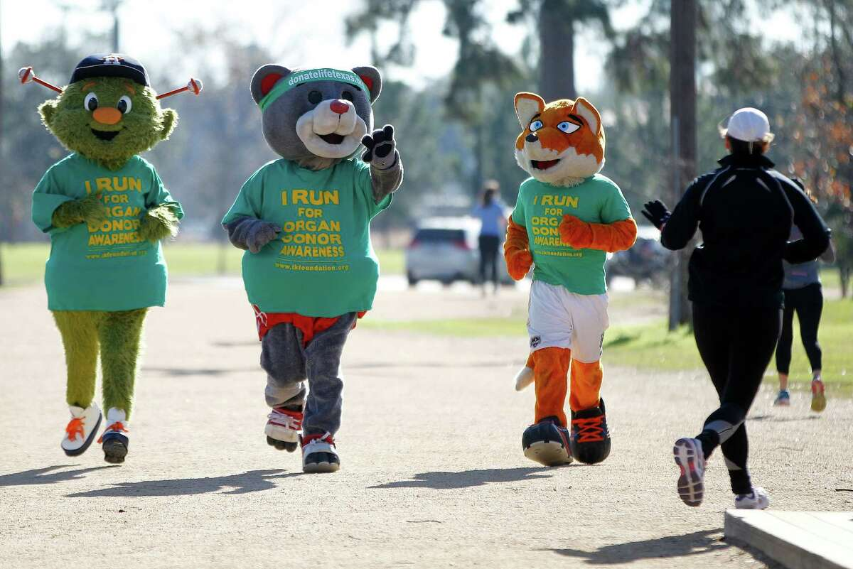 Clutch the Rockets mascot waves to a fellow runner as he, Orbit, the Astros mascot, and Dynamo's Diesel jog during the Houston Marathon Committee's annual