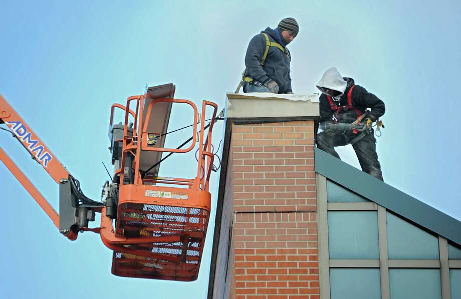 Construction workers are seen on top of the terminal at the Albany International Airport on Monday, Jan. 11, 2016 in Albany, N.Y.  (Lori Van Buren / Times Union) Photo: Lori Van Buren