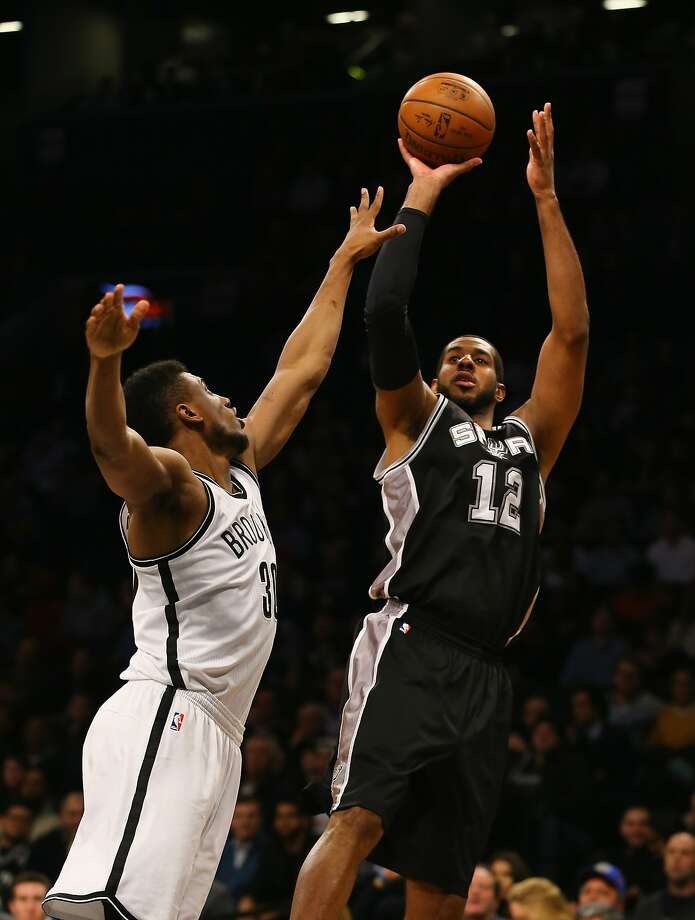 The Spurs' LaMarcus Aldridge, with a game-high 25 points, shoots against Thaddeus Young of the Nets. Photo: Al Bello, Getty Images