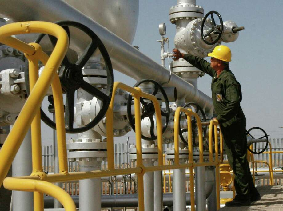 A  technician  checks oil field equipment in  Iran, which soon may begin selling crude  into  an already flooded market as western nations lift economic sanctions against the Islamic Republic. (AP Photo) Photo: Vahid Salemi, STR / AP