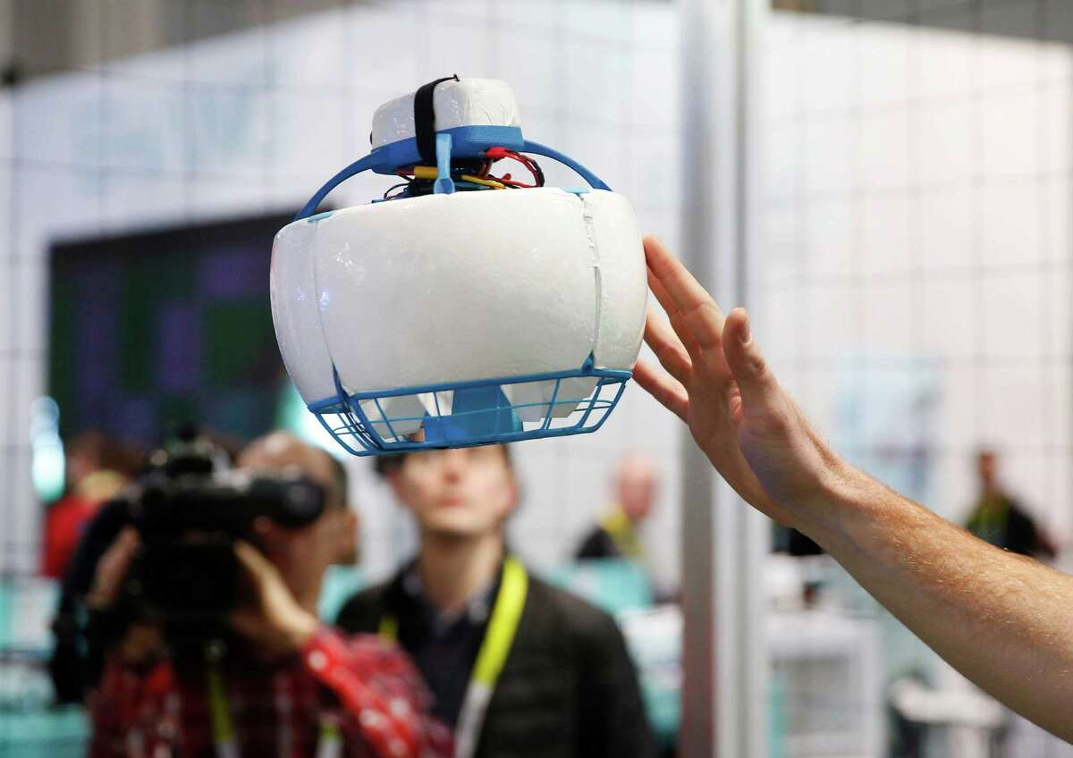 A Fleye drone is encased in what looks like a helmet to protect bystanders from its propellers.