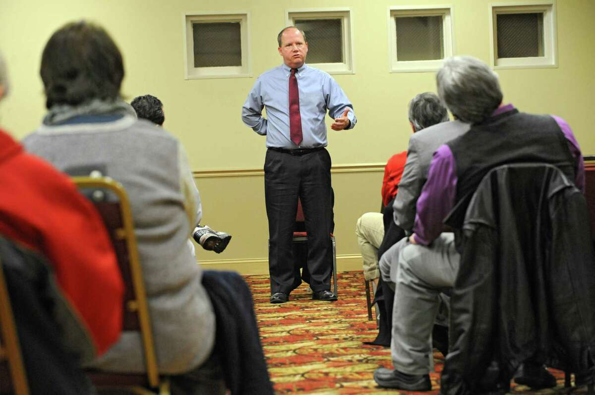 Richard McGinn Jr., of The University At Albany Foundation, center, answers a question from Donald Csaposs, right, as neighbors of the University at Albany attend a meeting at the Best Western on Western Ave. on Monday, Jan. 11, 2016 in Albany, N.Y. Representatives of UAlbany wanted to answer questions about the nearly nine wooded acres off Norwood Street and Waverly Place they recently purchased. (Lori Van Buren / Times Union)