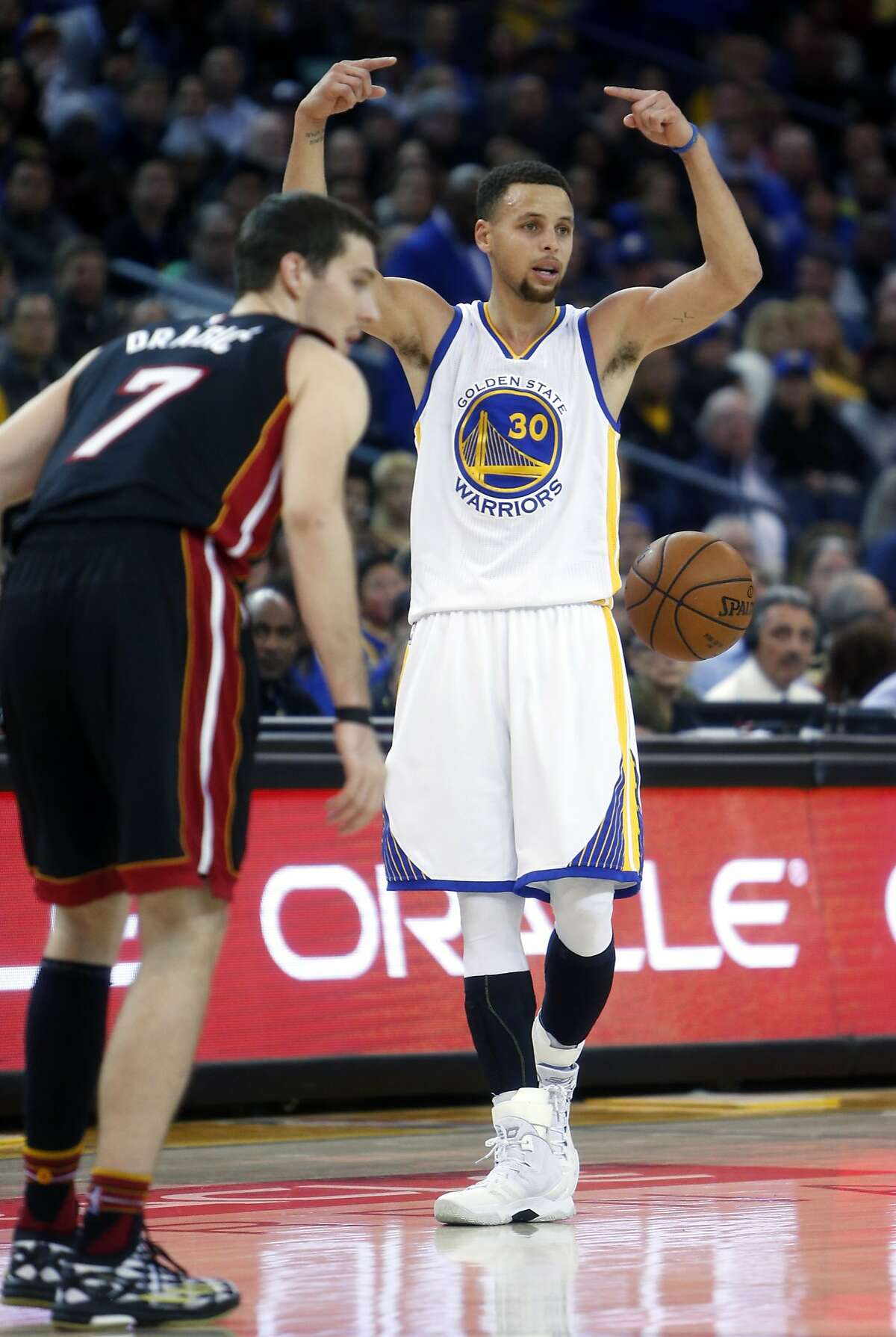 Golden State Warriors' Stephen Curry calls a play against Miami Heat's Goran Dragic in 2nd quarter during NBA game at Oracle Arena in Oakland, Calif., on Monday, January 11, 2016.