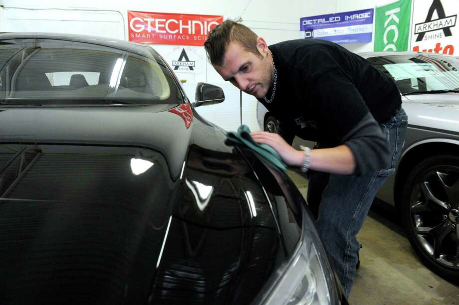 Kevin Awalt removes contaminates from the surface of a customer's car Wednesday, January 6, 2016. Awalt, 36, of Brookfield is the owner of Arkham Shine, an auto detailing shop in New Milford. Photo: Carol Kaliff / Hearst Connecticut Media / The News-Times