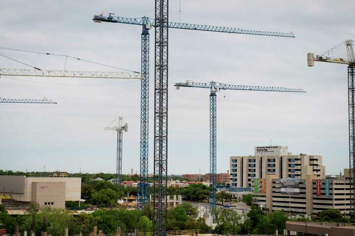 Construction cranes stand at the site of the future Dell Medical School's Research and Medical Office Buildings of the University of Texas at Austin campus in Austin, Texas, U.S., on Saturday, April 4, 2015. About 900,000 people live in the city of Austin and that number is expected to reach nearly 1.3 million by 2040, a 40 percent increase, according to city figures. More than 100 people move to the city a day, according to the city's demographer. Photographer: Matthew Busch/Bloomberg
