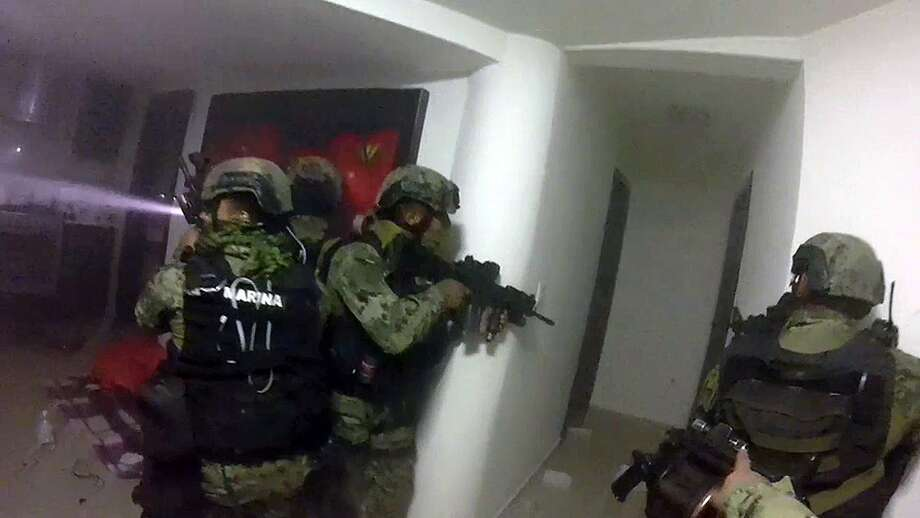 """Mexican  marines storm a home Friday during the operation to recapture Joaquin """"El Chapo"""" Guzman in Los Mochis city. It took troops about 15 minutes to secure the house. Photo: Associated Press"""