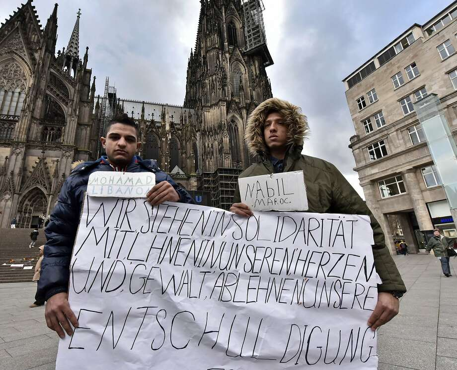 "Mohamad of Lebanon, left, and Nabil of Morocco hold a sign in Cologne that reads: ""We stand in solidarity in our hearts with you, we refuse violence and hope you accept our apology."" Photo: Martin Meissner, Associated Press"