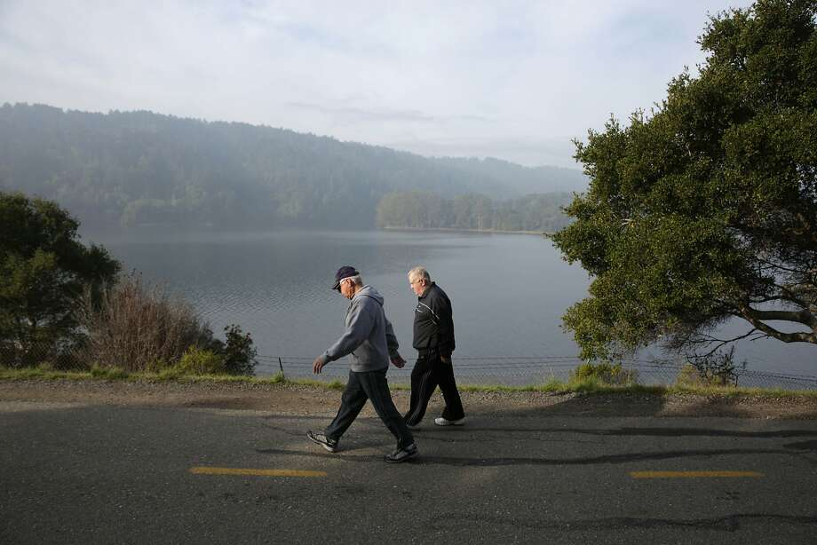People walk along a path next to Crystal Springs Reservoir, which is starting to show a slow return to normal. Photo: Lea Suzuki, The Chronicle