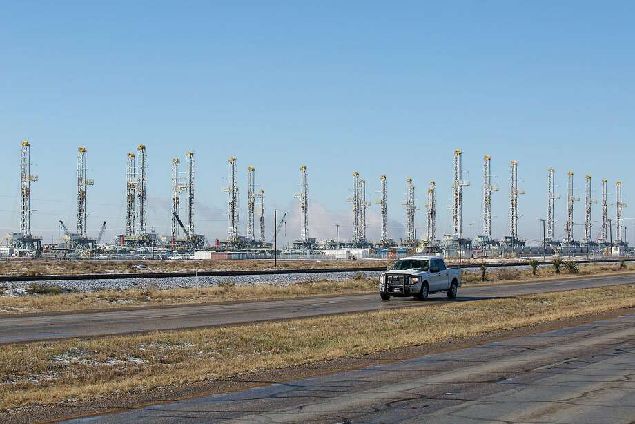 FILE - In this Wednesday, Feb. 25, 2015, file photo, more than 30 oil drilling rigs are idle in a Helmerich & Payne, Inc. yard in Odessa, Texas, along Highway 80, as rig counts drop in the Permian Basin. The price of oil continues to fall, extending a slide that has already gone further and lasted longer than most thought, and probing depths not seen since 2003. Lower crude prices are leading to lower prices for gasoline, diesel, jet fuel and heating oil, giving drivers, shippers, and many businesses a big break on fuel costs. But layoffs across the oil industry are mounting, and bankruptcies among oil companies are expected to soar. (Courtney Sacco/Odessa American via AP) MANDATORY CREDIT Photo: Courtney Sacco, Associated Press