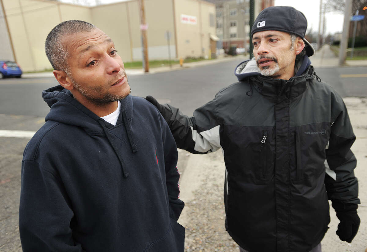 Angel Martinez, left, of Bridgeport, brother of Carmen Martinez, who was struck and killed by a pickup truck while crossing John Street on Monday, is consoled by neighbor Victor Nazario, right, near the location of the accident in Bridgeport, Conn. on Tuesday, January 12, 2016.