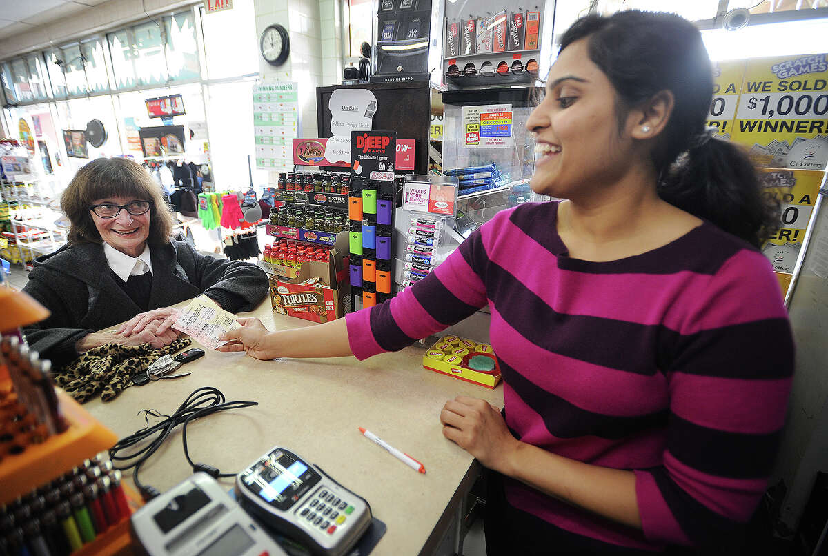 Arlene Skovira, of Fairfield, purchases six Powerball tickets from Bhumika Patel at News Express on Tunxis Hill Cutoff in Fairfield, Conn. on Tuesday, January 12, 2016. The jackpot had risen past $1.5 billion dollars as customers flooded the store for tickets.