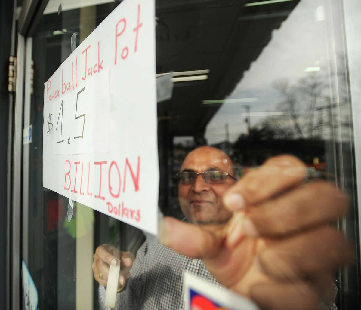 Ramesh Patel posts a revised Powerball jackpot total on the front door at News Express on Tunxis Hill Cutoff in Fairfield, Conn. on Tuesday, January 12, 2016. The jackpot had risen past $1.5 billion dollars as customers flooded the store for tickets.