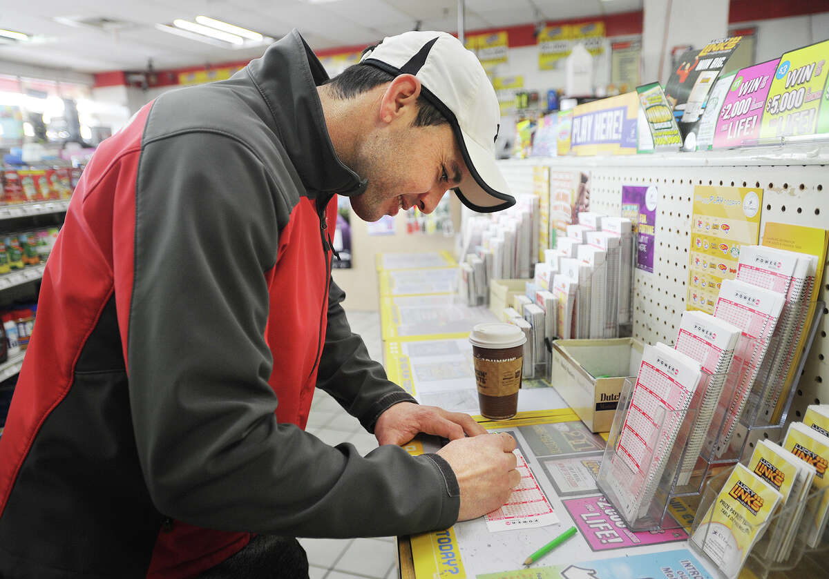 Geovane Dos Reis, of Bridgeport, fills out Powerball tickets at News Express on Tunxis Hill Cutoff in Fairfield, Conn. on Tuesday, January 12, 2016. The jackpot had risen past $1.5 billion dollars as customers flooded the store for tickets.