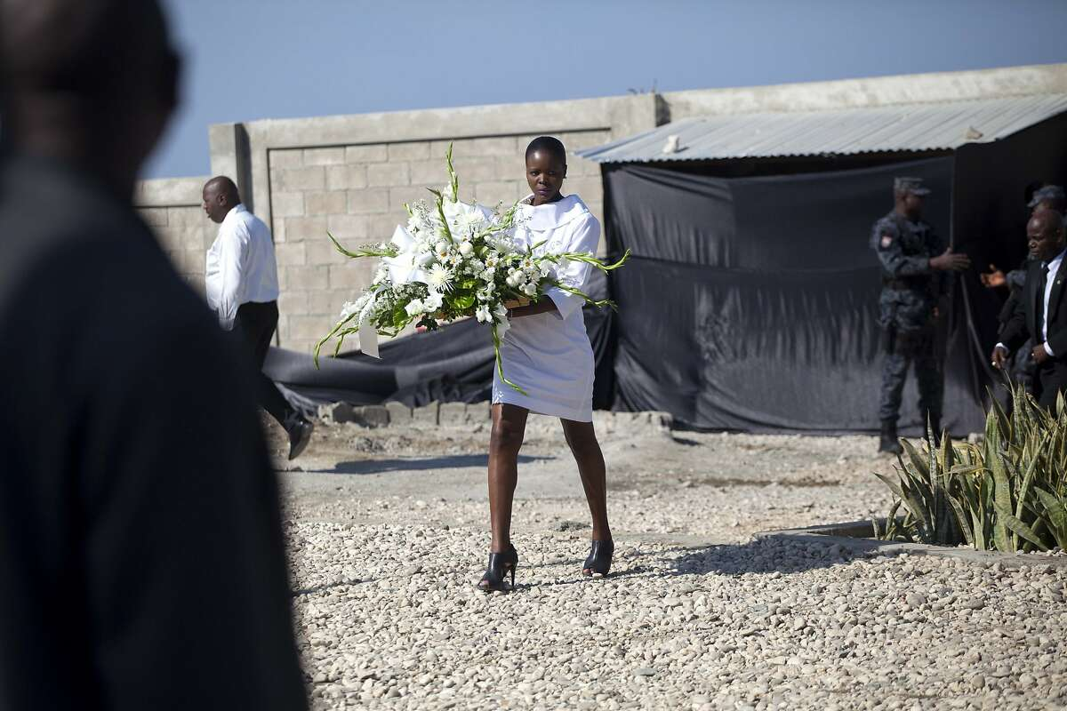 A woman arrives with a floral tribute at Titanyen, the mass burial site for victims of the 2010 earthquake, before the start of a memorial service marking the 6th anniversary of the quake, north of Port-au-Prince, Haiti, Tuesday, Jan. 12, 2016. Haitians gathered at prayer services to remember those who lost their lives. The government has said more than 300,000 people were killed, but the exact toll is unknown. (AP Photo/Dieu Nalio Chery)