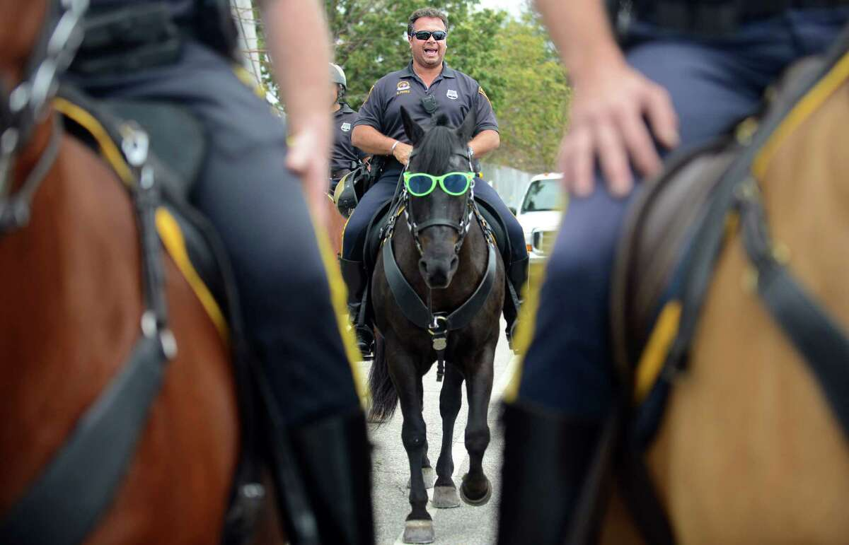 Bridgeport Police Officer Edgar Perez rides a bespectacled Nightmare, a horse in the mounted police unit, during the annual Gathering of the Vibes music festival Saturday, Aug. 2, 2014, at Seaside Park in Bridgeport, Conn.