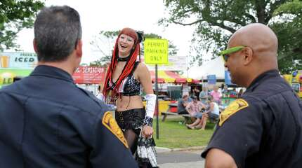 Sasha the Fire Gypsy talks with Bridgeport Police officers Friday, Aug. 1, 2014, at the annual Gathering of the Vibes music festival at Seaside Park in Bridgeport, Conn.