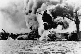 FILE-- The infamous attack on Pearl Harbor on December 7, 1941.  The USS Arizona is pictured in flames after the Japanese attack.   On Sunday, Dec. 7, 1997, the 56th anniversary of the attack that drew the United States into World War II, two Navy men who survived the battle are scheduled to have their ashes scattered on the waters above the battleship. It is an honor extended to those who survived the attack while serving on another ship, or those who served on the Arizona before the attack.(AP Photo/U.S. Navy,File)