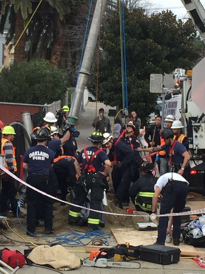 Oakland firefighters were working Tuesday afternoon to free a man stuck in a 10-foot-deep hole and pinned by debris on the 2300 block of 21st Avenue. Photo: Michael Macor