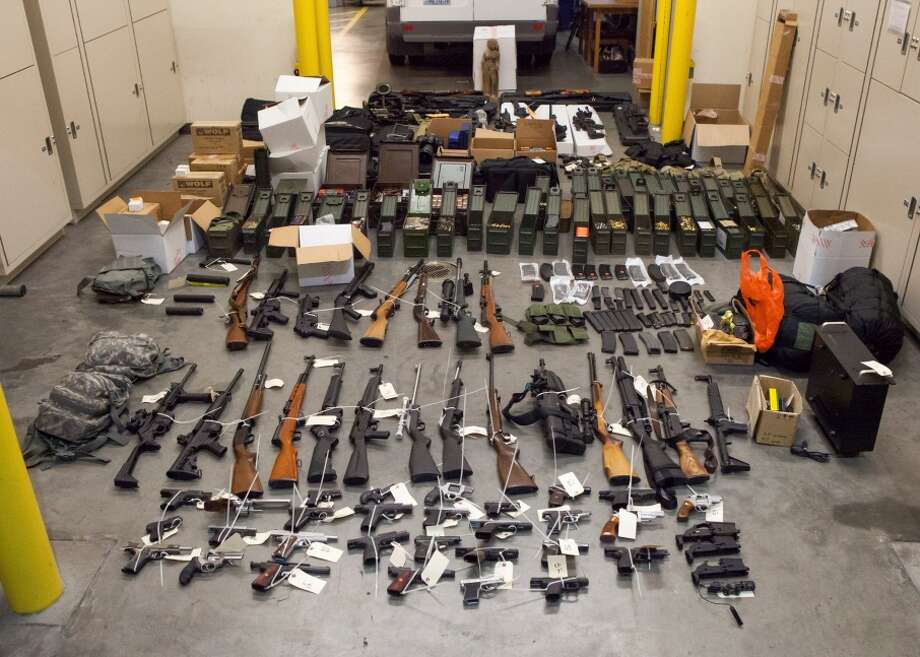 Seattle police seized 68 firearms and a pile of body armor and ammunition as part of a burglary investigation. They arrested a 38-year-old Bellevue man for investigation of burglary and theft of 17 guns. Photo: Courtesy Seattle Police Department