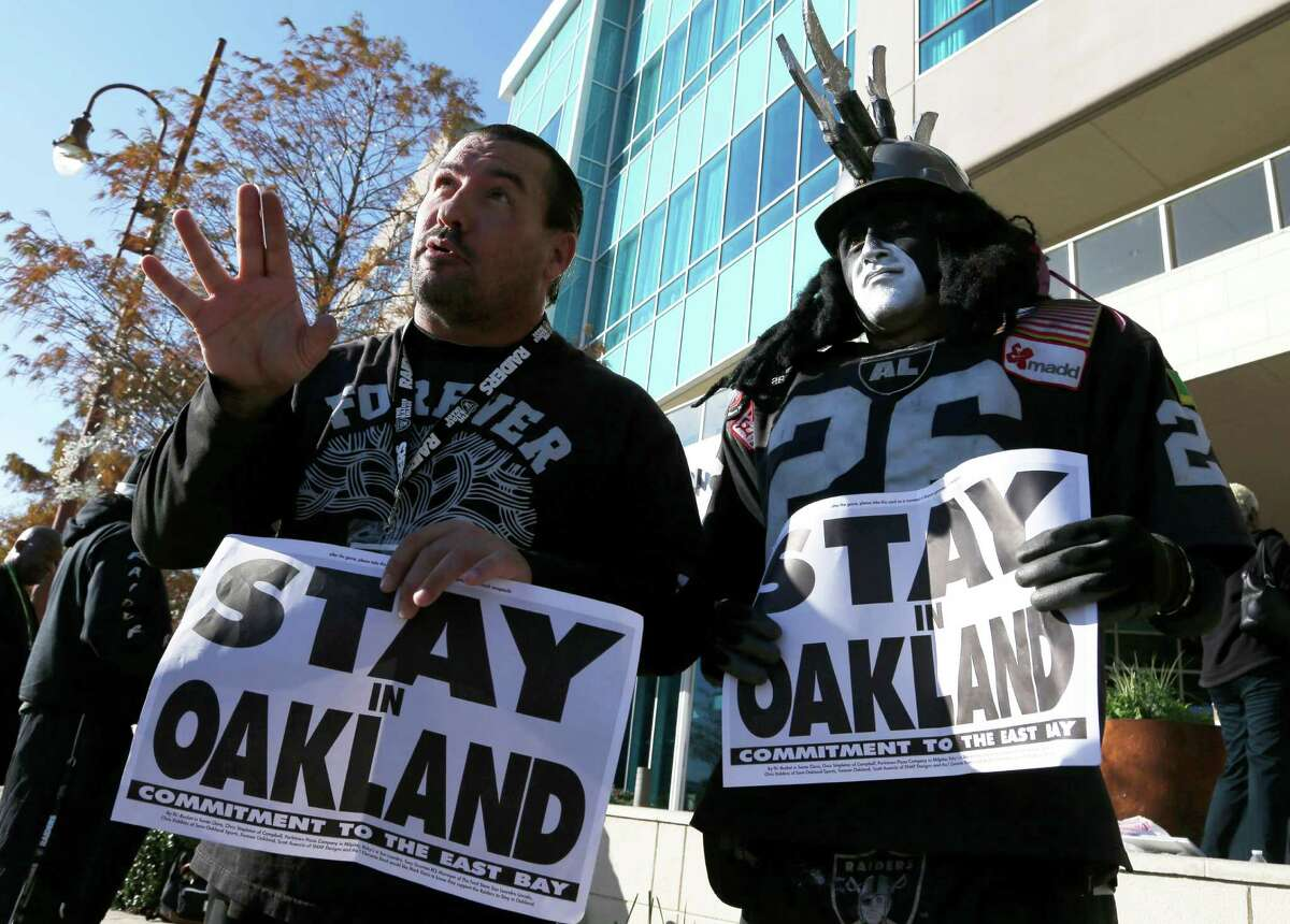 Oakland Raiders fans Griz Jones, left, and Ray Perez make their case for keeping the NFL football team in Oakland outside the hotel where NFL owners are meeting Tuesday, Jan. 12, 2016, in Houston to discuss possible relocation to Los Angeles.