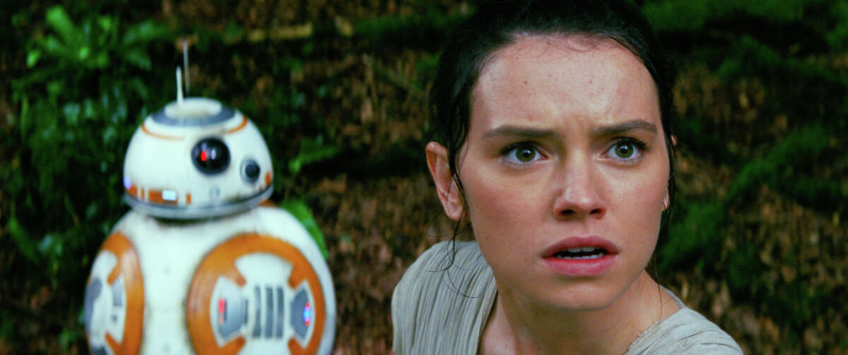 This photo provided by Disney/Lucasfilm shows Daisy Ridley, right, as Rey, and BB-8, in a scene from the film,