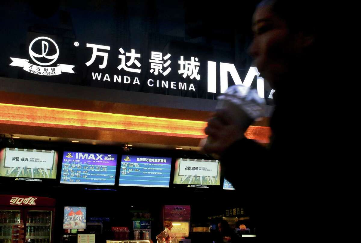 A Chinese moviegoer walks into the Wanda Cinema at the Wanda Group building in Beijing, Tuesday, Jan. 12, 2016. Wanda Group announced Tuesday it is buying Hollywood's Legendary Entertainment, the maker of films such as