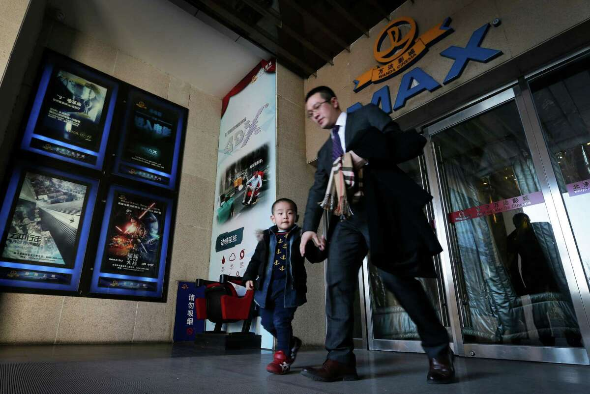 A man and his son walk out from the Wanda Cinema at the Wanda Group building in Beijing, Tuesday, Jan. 12, 2016. Wanda Group announced Tuesday it is buying Hollywood's Legendary Entertainment, the maker of films such as