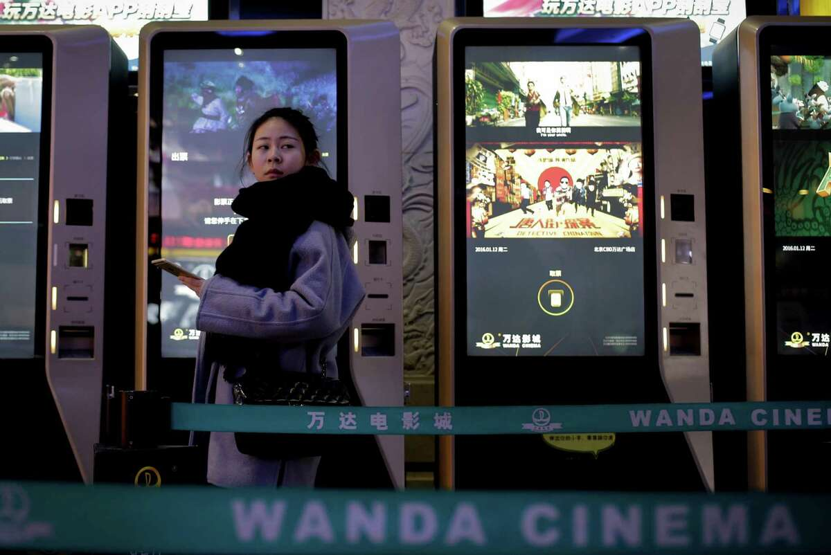 A woman walks past movie tickets collecting machines at the Wanda Cinema in Beijing, Tuesday, Jan. 12, 2016. Wanda Group announced Tuesday it is buying Hollywood's Legendary Entertainment, the maker of films such as