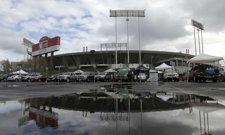 In this Dec. 24, 2015, O.co Coliseum is reflected in a puddle before an NFL football game between the Oakland Raiders and the San Diego Chargers in Oakland, Calif.(AP Photo/Jeff Chiu, File)