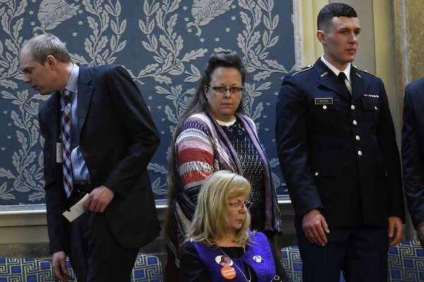 Kim Davis (C), the Rowan County clerk in Kentucky, arrives before US President Barack Obama delivers the State of the Union Address during a Joint Session of Congress at the US Capitol in Washington, DC, January 12, 2016. Kim Davis, a born-again Christian, was jailed briefly in September 2015 for contempt of court after refusing to issue marriage  licenses due to her opposition to gay marriage, which the Supreme Court legalized across the United States in June. Barack Obama will give his final State of the Union address, perhaps the last big opportunity of his presidency to sway a national audience and frame the 2016 election race. AFP PHOTO / SAUL LOEBSAUL LOEB/AFP/Getty Images