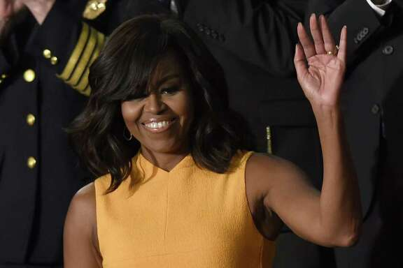 US First Lady Michelle Obama (C) waves before the arrival of US President Barack Obama before the State of the Union Address during a Joint Session of Congress at the US Capitol in Washington, DC, January 12, 2016. Barack Obama will give his final State of the Union address, perhaps the last big opportunity of his presidency to sway a national audience and frame the 2016 election race. AFP PHOTO / SAUL LOEB / AFP / SAUL LOEB        (Photo credit should read SAUL LOEB/AFP/Getty Images)