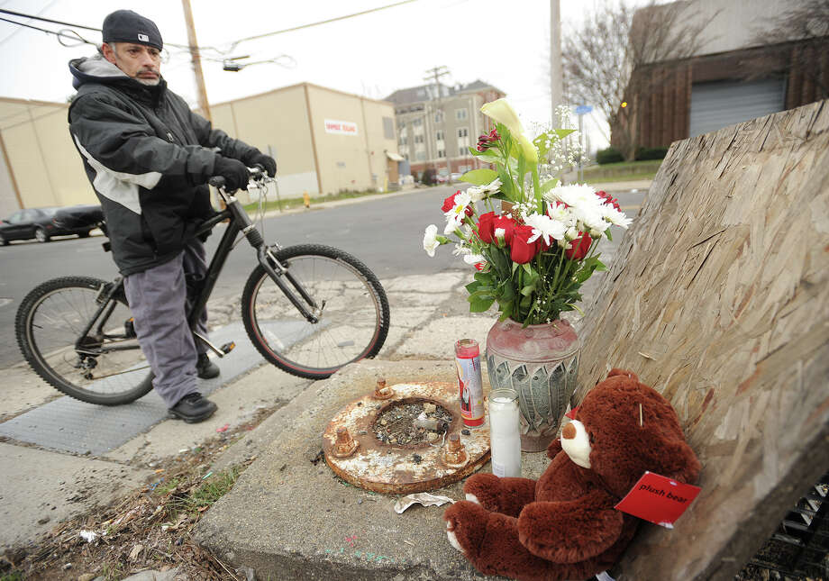 Victor Nazario, neighbor of Carmen Martinez, who was struck and killed by a pickup truck while crossing John Street on Monday, visits a memorial to her near the location of the accident in Bridgeport, Conn. on Tuesday, January 12, 2016. Photo: Brian A. Pounds / Hearst Connecticut Media / Connecticut Post