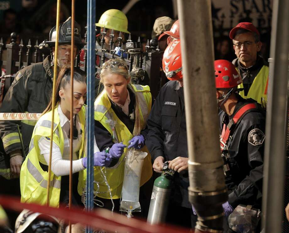Medical personnel lower an intravenous bag into the hole as Oakland and Alameda County firefighters and emergency personnel worked to free a plumber who was trapped when the hole he was working in collapsed around him in Oakland, Calif., on Tuesday, January 12, 2016. Photo: Carlos Avila Gonzalez, The Chronicle