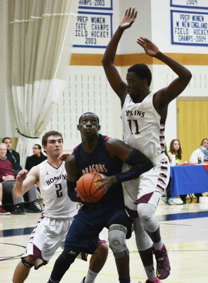 Forward Sunday Okeke (Darien) takes on two Hopkins defenders in his first game back after sustaining a knee injury at the beginning of the season. Okeke had 8 points, 11 rebounds, five steals and five assists in his team's 63-62 overtime win Jan. 7. Photo: Contributed / Darien News