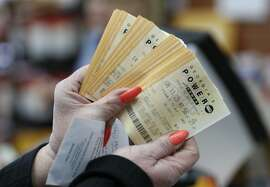 A lottery player displays Powerball lottery tickets at a Pilot convenience store, Wednesday, Jan. 13, 2016, in Tallapoosa, Ga. (AP Photo/John Bazemore)