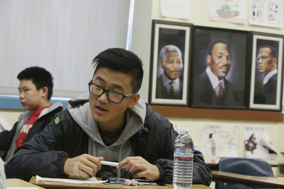 Freshman David Chen (right) sits next to portraits of Nelson Mandela, Martin Luther King, Jr and Malcolm X while working with classmates on a class assignment during ethnic studies class at Washington High School on Wednesday, January 13, 2015 in San Francisco, Calif.