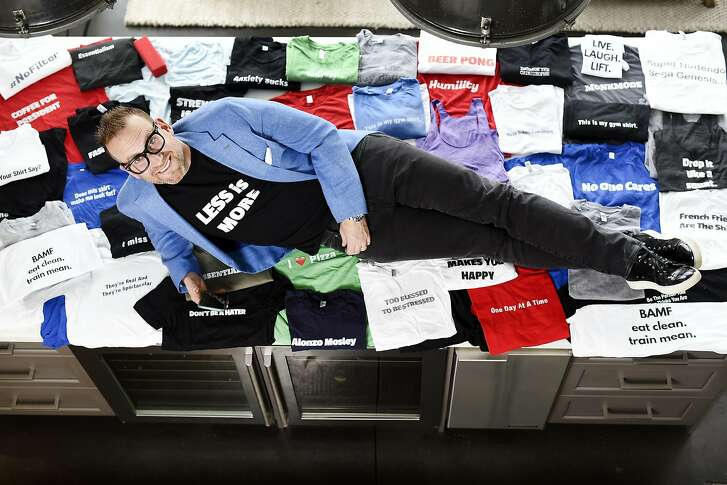 Tyler Mitchell, founder of new app Levatee, poses for a portrait with a pile of T-shirts at his home in San Francisco, CA on Tuesday, January 12, 2016. Tyler's app Levatee allows users to design a T-shirt in multiple colors, with sayings in multiple fonts and sizes, using any words they want, in 30 seconds, for less than $30.
