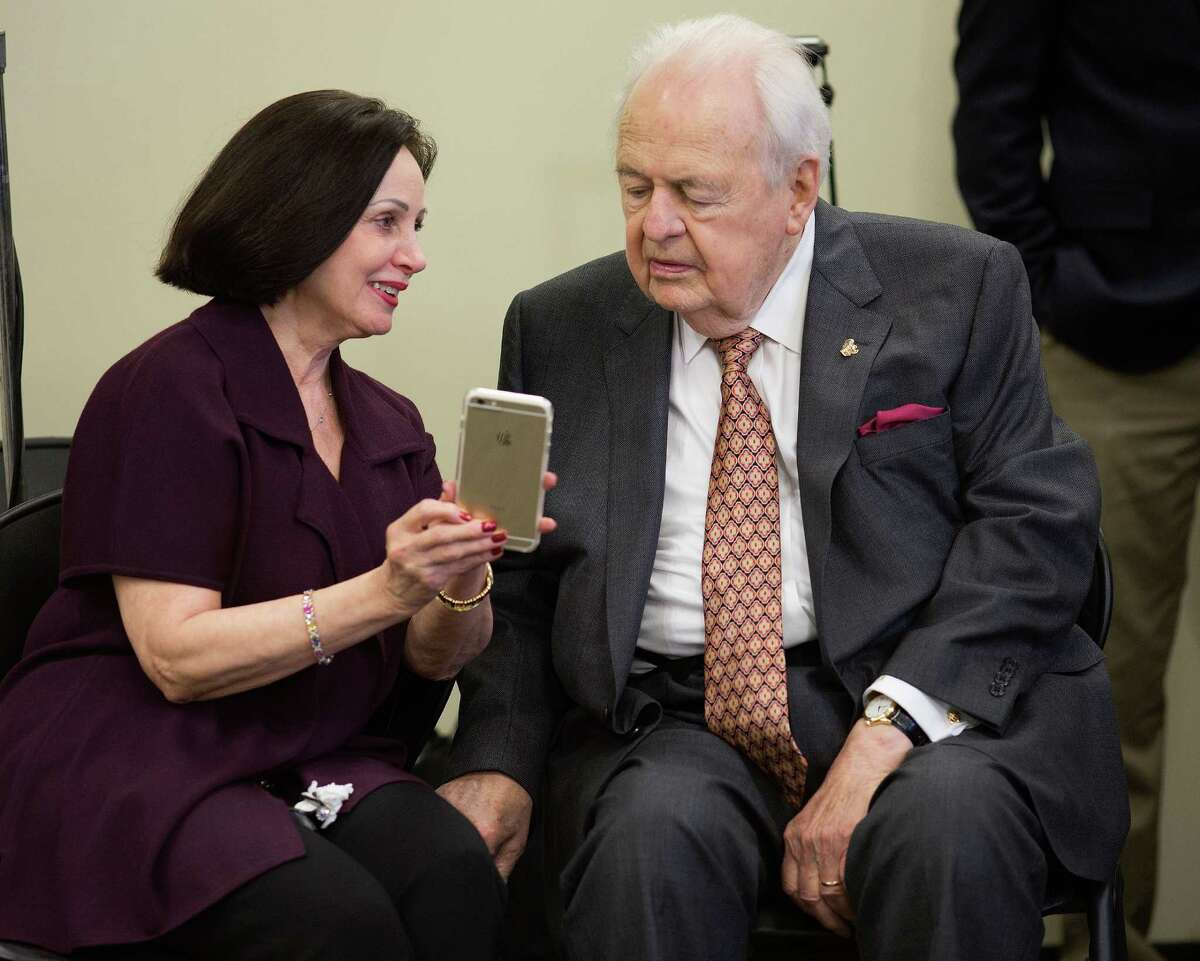 Tom Benson and his wife, Gayle, look at a cellphone as they wait for the start of a NFL news conference earlier this year.