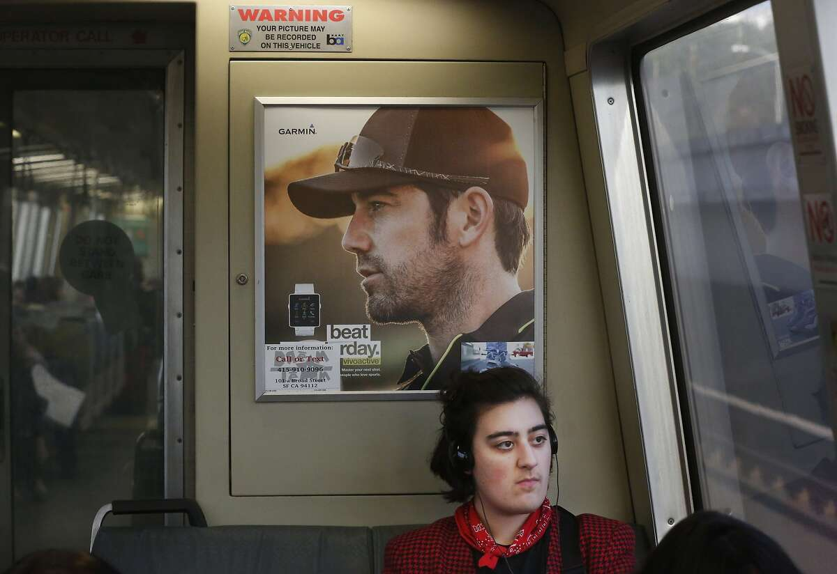 A sign warning passengers that their picture may be recorded is seen above Hannah Moore on a train headed for SFO that has fake security cameras Jan. 13, 2015 near Oakland, Calif.